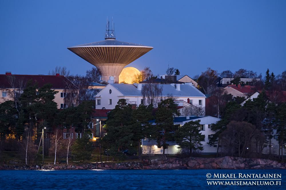 Lauttasaaren vesitorni ja kuu Jätkäsaaresta, Helsinki (342 mm, exposure blend, pisin valotus 0.4 sekuntia, ISO 1600, puuskissa arviolta noin 15 m/s tuulta, jalusta ei täydessä korkeudessa, kuvat ajoitettu lankalaukaisimella puuskien väliin, silti merkittävä osa kuvista epäteräviä)
