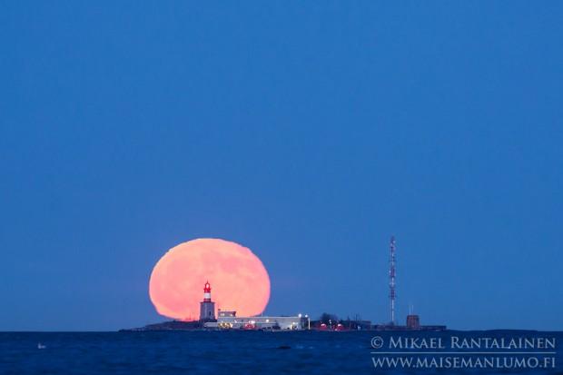 Kuu nousee Harmajan majakan takaa Lauttasaaresta kuvattuna / Linkki Kuukuvia galleriaan